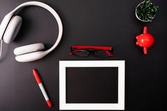 Πρότυπο, πλαίσιο φωτογραφιών, ακουστικά, γυαλιά, μάνδρα, και κάκτος Το κόκκινο και γράφει το αντικείμενο στο μαύρο υπόβαθρο στοκ εικόνες