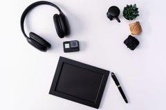 Πρότυπο, πλαίσιο φωτογραφιών, κάμερα δράσης, ακουστικά, μάνδρα, και κάκτος, μαύρο αντικείμενο στο άσπρο υπόβαθρο στοκ εικόνες