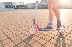 Πόδια και ρόδινο μηχανικό δίκυκλο λακτίσματος στο υπόβαθρο του ηλιοβασιλέματος Κορίτσι που οδηγά ένα τετράγωνο πόλεων σε ένα ρόδι στοκ εικόνες