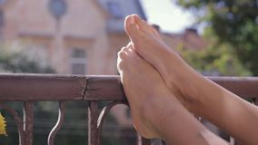 Πόδια της γυναίκας κινηματογραφήσεων σε πρώτο πλάνο στα παλαιά ξύλινα κιγκλιδώματα μπαλκονιών στο παλαιό υπόβαθρο σπιτιών απόθεμα βίντεο