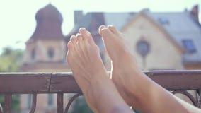 Πόδια της γυναίκας κινηματογραφήσεων σε πρώτο πλάνο στα παλαιά ξύλινα κιγκλιδώματα μπαλκονιών στο παλαιό υπόβαθρο σπιτιών φιλμ μικρού μήκους
