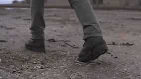 Πόδια του ατόμου στα βαριά παπούτσια moutaineer που περπατούν από τη λάσπη στη νεφελώδη χέρσα περιοχή φιλμ μικρού μήκους