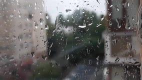 Πτώσεις νερού σε ένα παράθυρο με το θολωμένο υπόβαθρο Εστίαση στις σταγόνες βροχής Άποψη στην οδό φιλμ μικρού μήκους