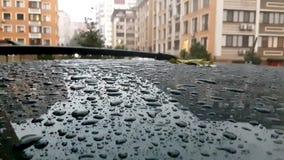 Πτώση βροχής στη στέγη του μαύρου αυτοκινήτου που σταθμεύουν στο δρόμο Βρέχοντας ημέρα απόθεμα βίντεο