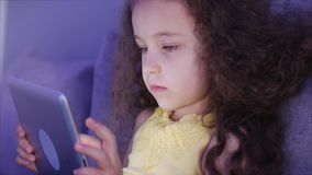 Πυροβοληθε'ν νύχτα πορτρέτο ενός καυκάσιου χαριτωμένου παιδιού, λίγος στενός επάνω κοριτσάκι του προσώπου ενός παιδιού που βλέπει φιλμ μικρού μήκους