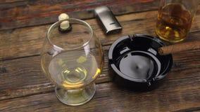 πυροβολισμός ολισθαινόντων ρυθμιστών Ένα πούρο ashtray και ένα γυαλί του οινοπνεύματος είναι στον παλαιό πίνακα φιλμ μικρού μήκους