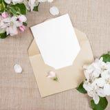ï ¿ ½ ard met een beige envelop en witte bloemen van appelboom op beige stof Stock Afbeeldingen