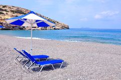 Blue lounge chairs and beach umbrella. Ð¡hairs and beach umbrella on the coast of Mediterranean royalty free stock photo
