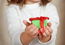 Сhild holding Christmas present Stock Images