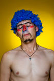 Ð¡lown in a blue wig, expressing surprise Stock Photos