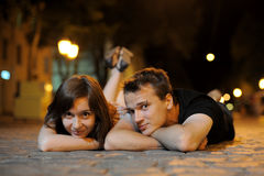 Ð¡ouple laying on a road in the evening Royalty Free Stock Image