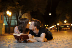 Сouple laying on a road and kissing Stock Images