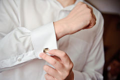 Ð¡uff links. A man putting on his cuff links royalty free stock photography