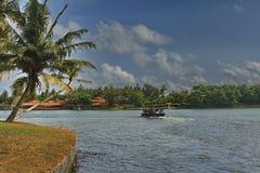 Тропический залив с плывущей лодкой и с видом на тропический лес. Exotic tropical Bay with a floating boat Stock Photos