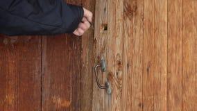Ьan öppnar den roterande tangenten i lås och den gamla dörren arkivfilmer