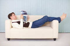Ьan lies comfortably on sofa with a newspaper Royalty Free Stock Image