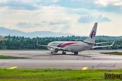 Авиакомпания Малайзии самолета ездя на такси к взлетно-посадочной дорожке в аэропорте стоковая фотография