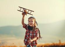 Авиатор пилота ребенка с мечтами самолета путешествовать летом на заходе солнца стоковая фотография rf