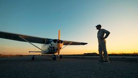 Авиатор стоит на взлетно-посадочной дорожке около самолета, конца вверх акции видеоматериалы