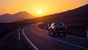 Автомобиль на извилистой дороге управляя к заходу солнца стоковые фотографии rf