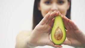 Авокадо для здорового тела Красивая маленькая девочка держит половину авокадоа в ее руках и показывает ее на расплывчатом космосе акции видеоматериалы