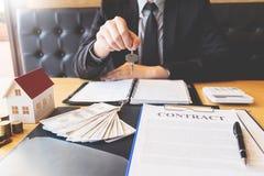 Агент по продаже недвижимости давая дом пользуется ключом свойство согласования знака клиента для продажи, покупающ и продающ кон стоковые фото