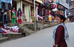 Азиатская женщина на улицах Khandbari идя к магазину, Непалу стоковые изображения