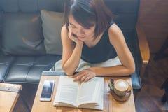 Азиатская женщина прочитала книгу в свободном времени стоковая фотография rf