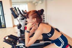 Азиатская маленькая девочка делая exrecises с гантелью в спортзале, смотря ее тело через зеркало на утре стоковые фотографии rf
