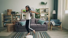 Азиатская молодая дама технология enjoyig современная слушая музыку в беспроводных наушниках и танцуя hoover промежутка времени р видеоматериал