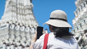 Азиатская дама фотографирует Wat Arun со смартфоном движение медленное Главная пагода на предпосылке сток-видео