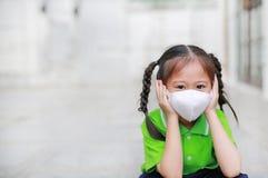 Азиатская девушка ребенка нося маску защиты пока снаружи к против премьер-министру 2 загрязнение воздуха 5 с указывать вверх в го стоковая фотография