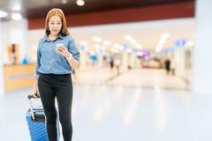 Азиатские женщины путешественника ища полет в смартфон на концепции перемещения крупного аэропорта стоковая фотография rf