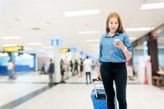 Азиатские женщины путешественника ища полет в смартфон на концепции перемещения крупного аэропорта стоковое изображение