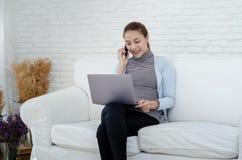 Азиатские женщины усмехающся и говорящ по телефону стоковое изображение