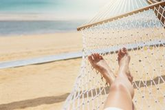 Азиатские женщины ослабляя в летнем отпуске гамака на пляже стоковое фото