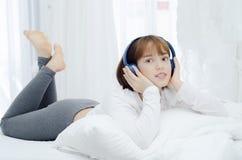 Азиатские женщины отдохнули в комнате Она была усмехающся и слушающ к музыке стоковое фото rf