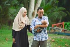 Азиатские мусульманские мать hijabi и прогулка отца через парк с сыном в прогулочной коляске пока его мама позаботить об ее todle стоковое изображение