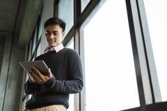 Азиатский молодой бизнесмен используя ПК планшета стоковая фотография