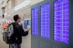 Азиатский человек с путешественником рюкзака используя умный мобильный телефон для регистрации на экране данным по полета в совре стоковая фотография
