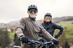 Активные старшие пары с electrobikes стоя outdoors на дороге в природе стоковое фото rf