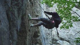 Альпинист близкого взгляда идет вниз со скалистой скалы с веревочкой безопасности сток-видео