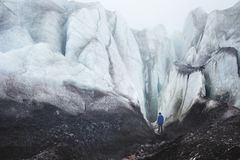 Альпинист с осью льда стоит на ноге большего ледника рядом с эпичным отказом в тумане в горах стоковая фотография