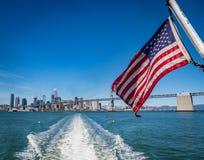 Американский флаг развевая с горизонтом Сан-Франциско и мостом залива стоковые фотографии rf