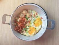 Английский завтрак состоит из яичницы, фасолей, бекона и гарнира с душистым стоковое фото