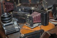 Античная складывая камера с мембранами в куче старых камер стоковая фотография