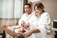 Апеллирующ жена наблюдая, как ее прекрасный человек имел очень вкусный завтрак стоковая фотография