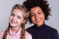 Апеллирующ милые дети стоя совместно и обнимать стоковые фото