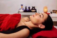 Апеллирующ темн-с волосами женщина с ponytail спокойно отдыхая в шкафе массажа стоковое фото rf