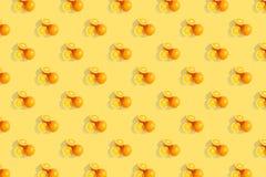 Апельсины на яркой покрашенной желтой предпосылке Повторение картины, подготовка для настроения цитруса обоев стоковое фото rf